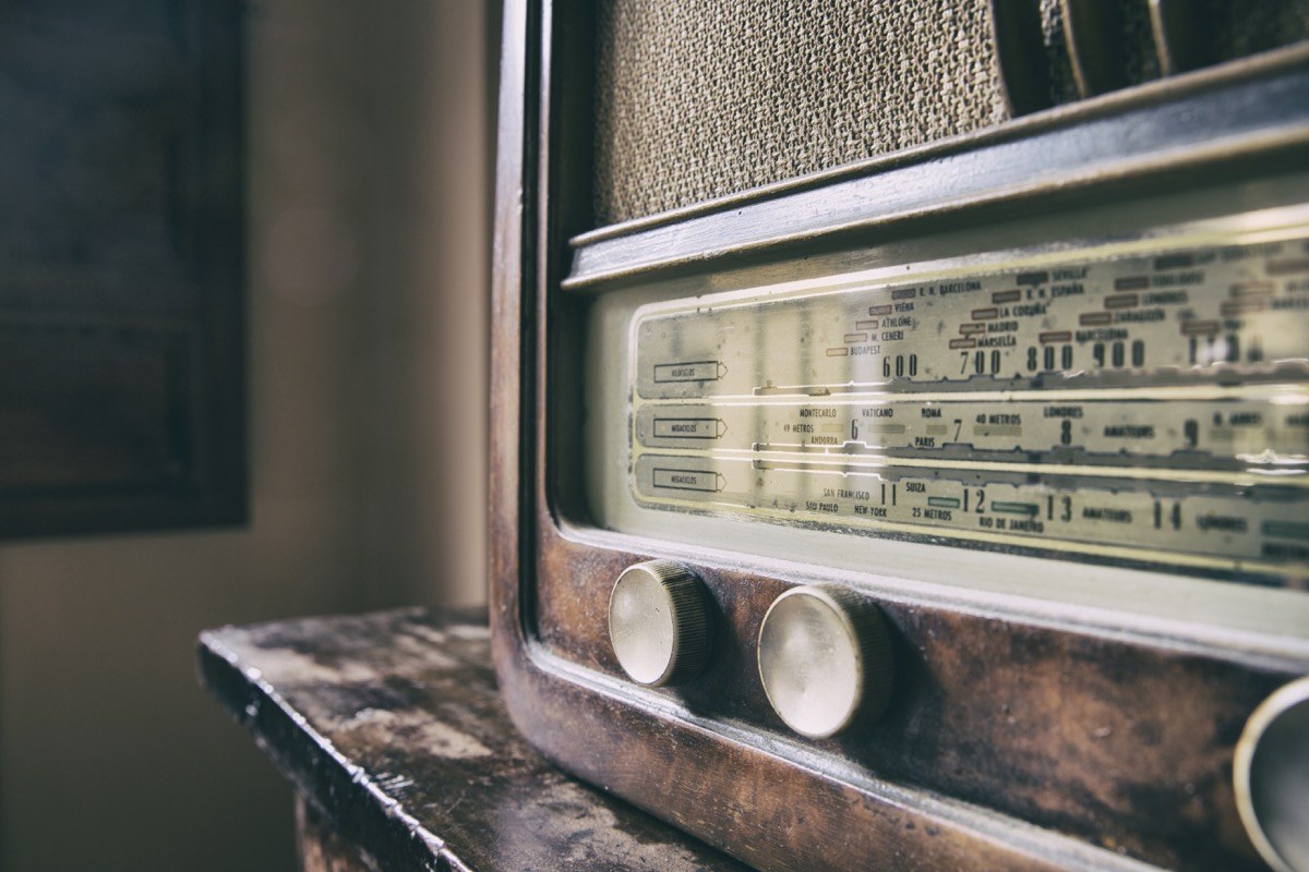 Obsolete radio in wooden case sits on antique table, state fact about kentucky