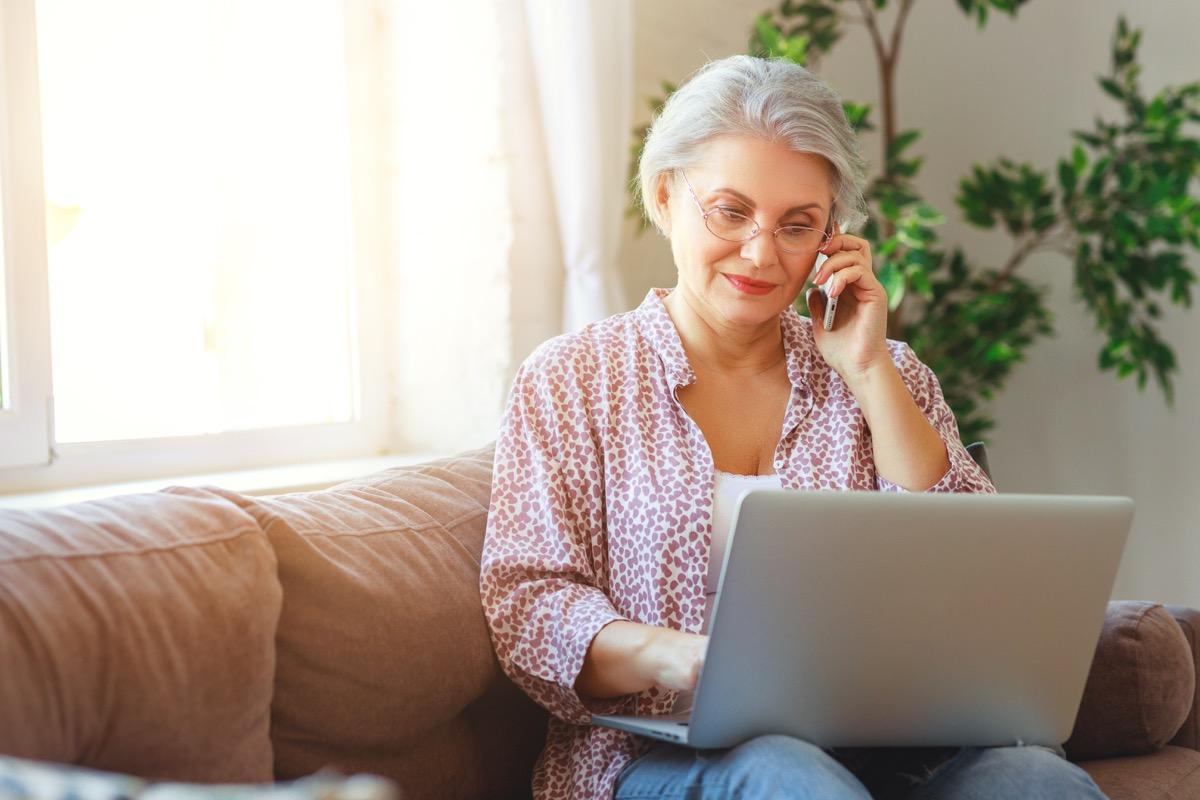 Older woman on laptop and phone call