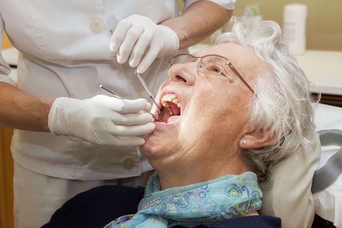An Older Woman Getting Her Mouth Checked Out at the Dentist, subtle symptoms of serious disease