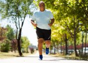 Overweight black man running outside getting some exercise in