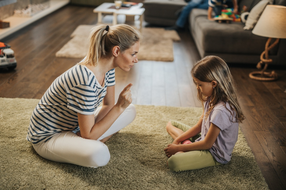 parent getting on to her kid in living room