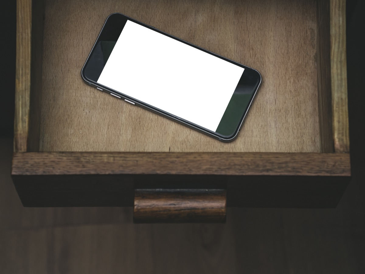 A phone in a nightstand drawer