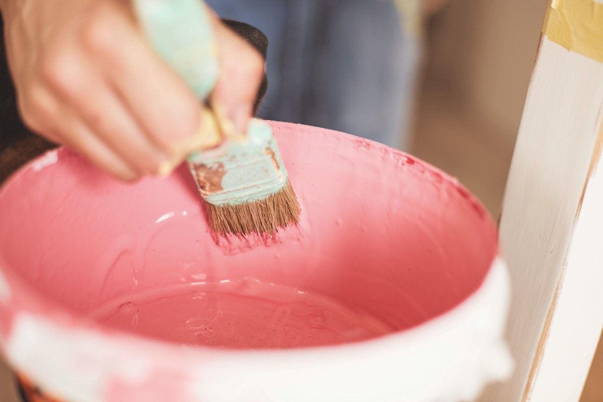 Close-up view of female craftperson taking pink paint from the can using paintbrush.
