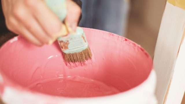 woman dipping brush into paint