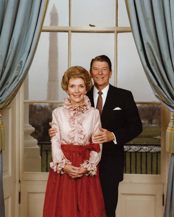 President Reagan and Mrs. Reagan pose in the Blue Room for their official portrait, nancy wearing ruffled shirt, 1980s fashion