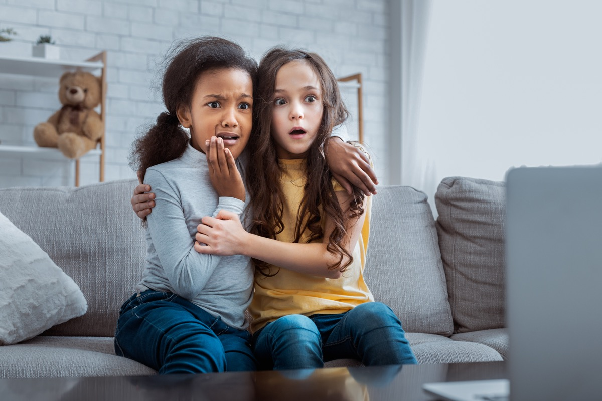scared girls watching horror movie on tv