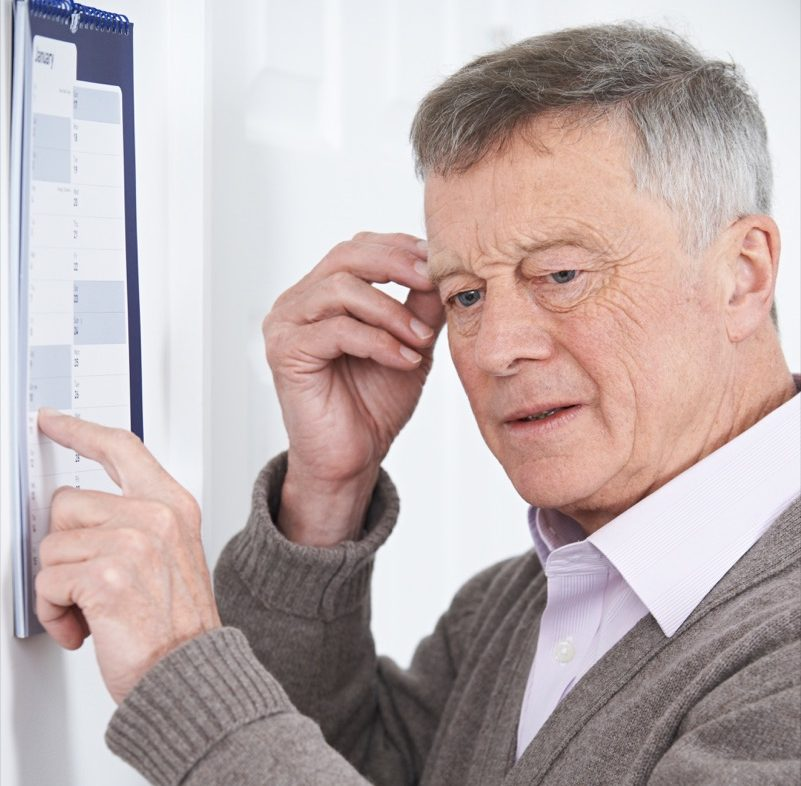 Senior man looking at a calendar confused