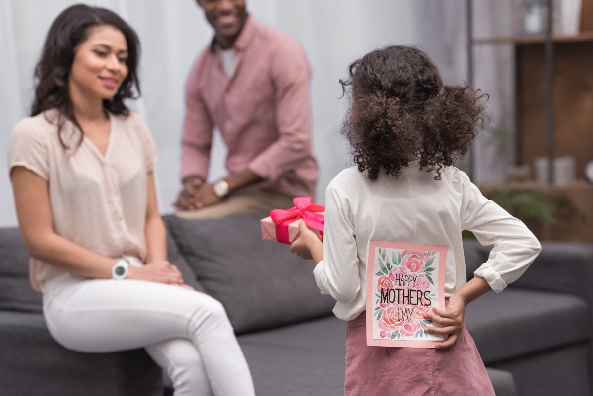 little black girl approaches mother sitting on grey couch with a gift and a happy mother's day card behind her back, state fact about west virginia