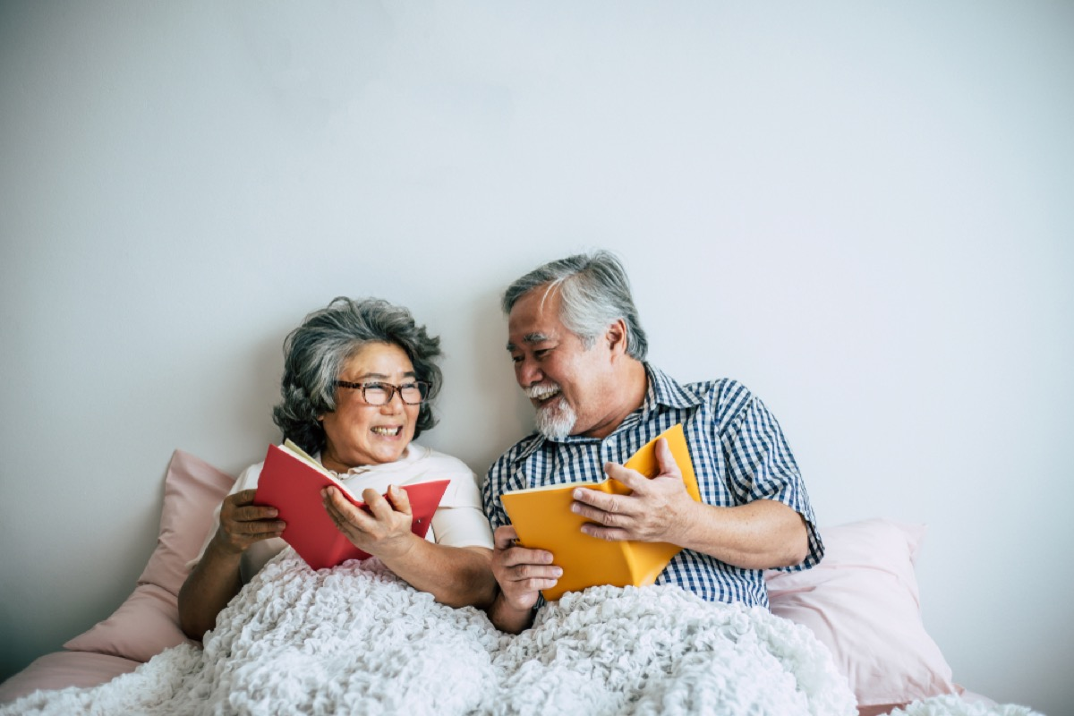 senior asian couple reading in bed