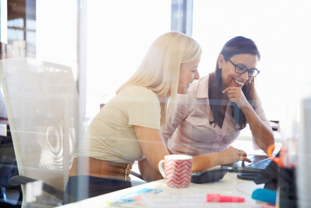 two women joking around their desk, how parenting has changed