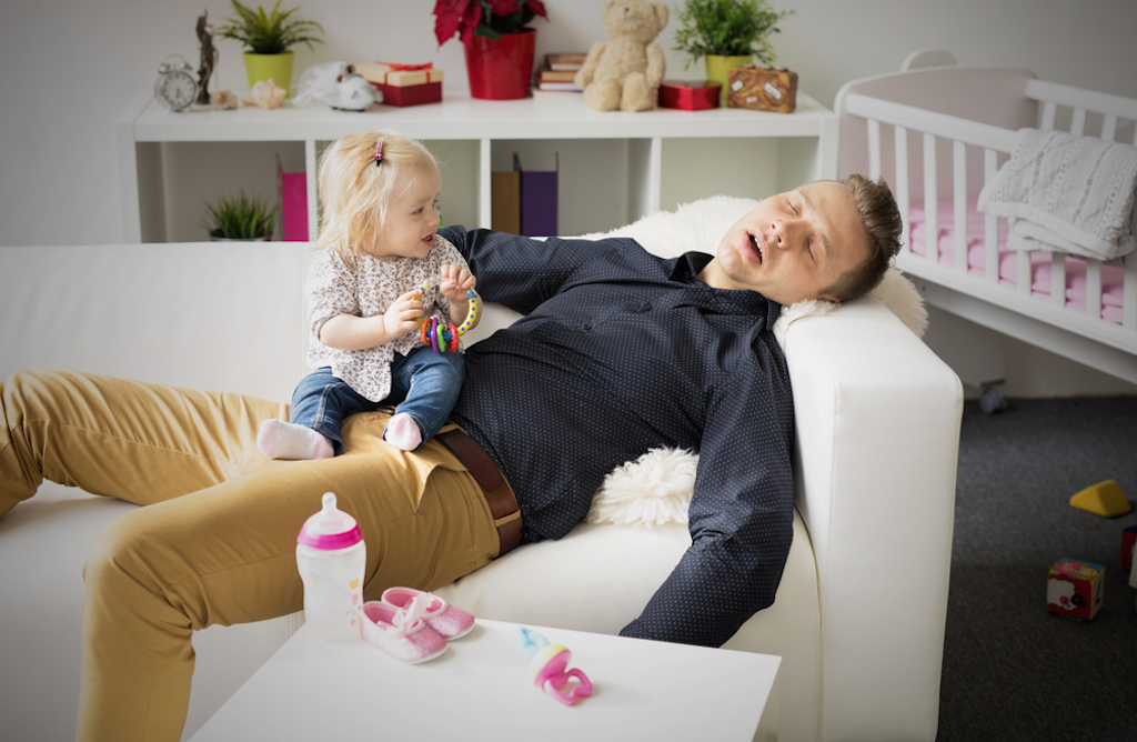tired father asleep while holding son