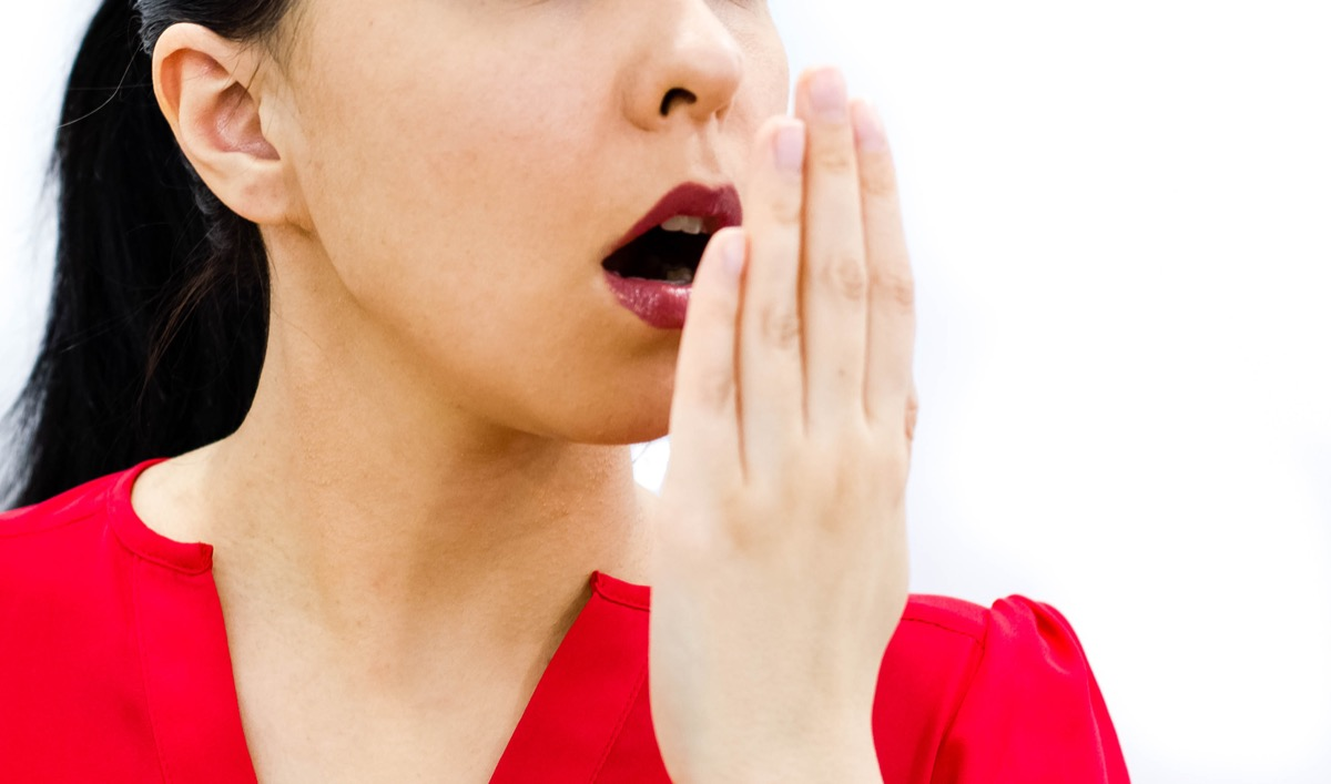 Woman smelling her breath