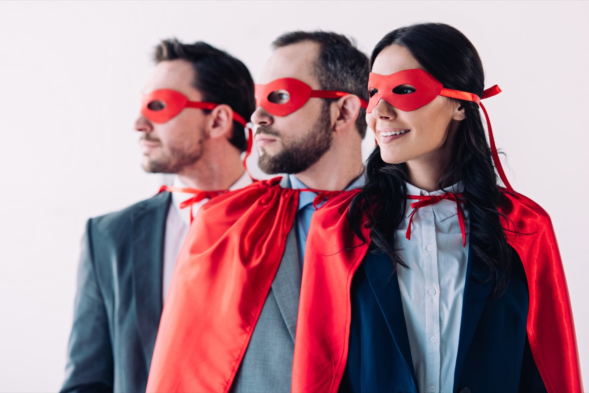 super businesspeople in masks and capes looking away in line in office - Image
