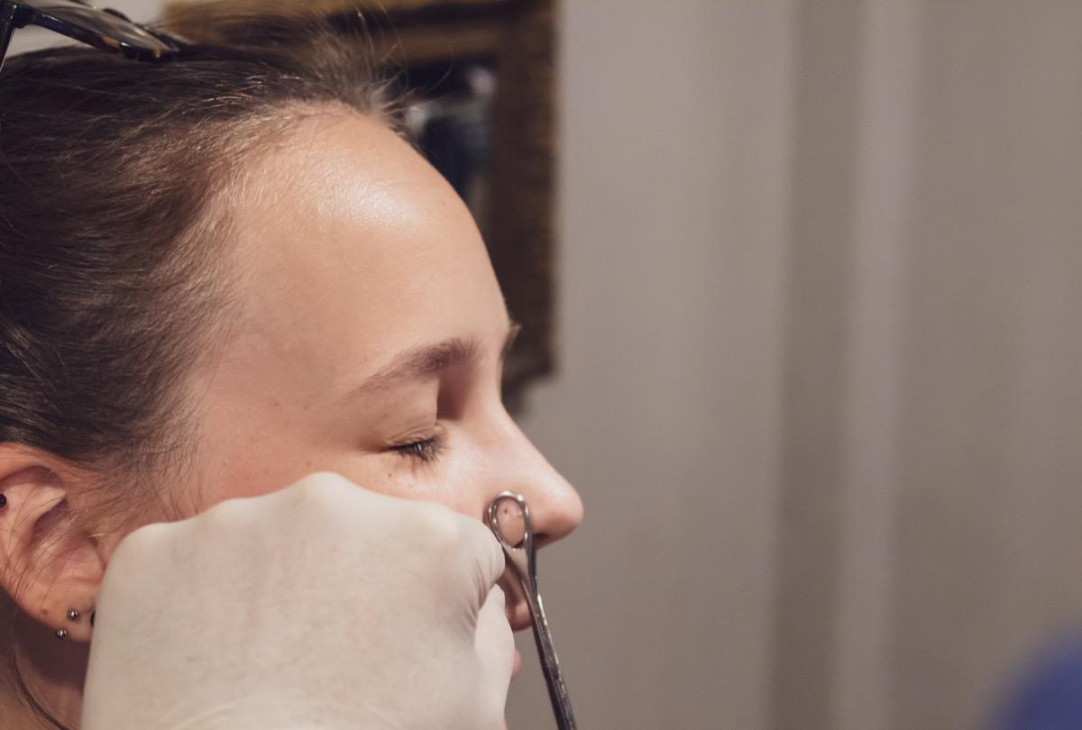 teenage girl getting nose ring