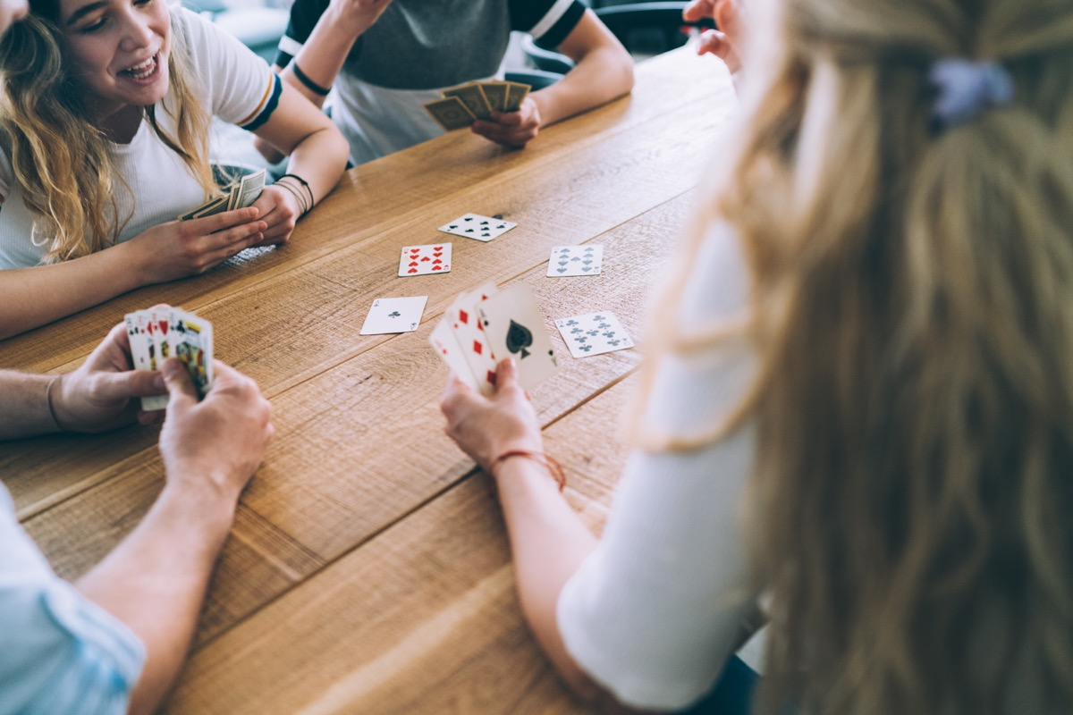 teenage kids playing a round of cards