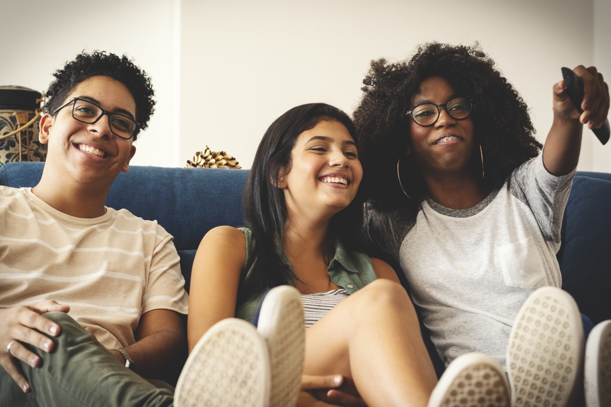 three teenagers watching tv together