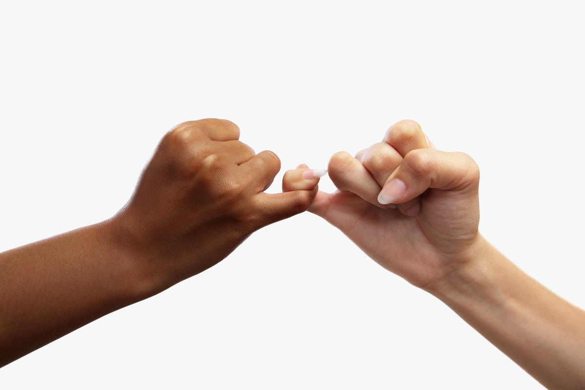 one white hand and one black hand making pinkie promise
