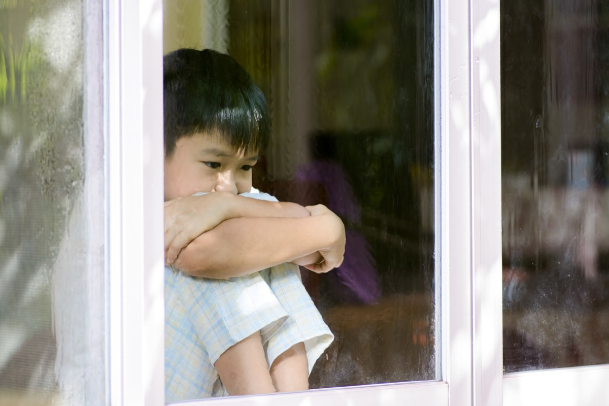 upset sad boy sitting by the window looking out of it, skills parents should teach kids