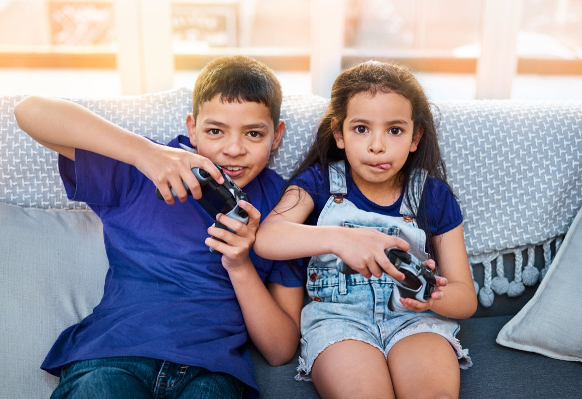 two kids sitting and playing video games by the couch