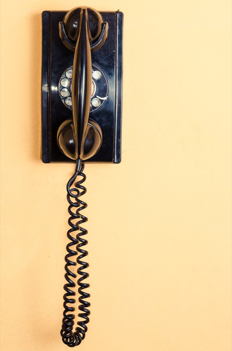 old black telephone with rotary disc on Yellow wall - Image