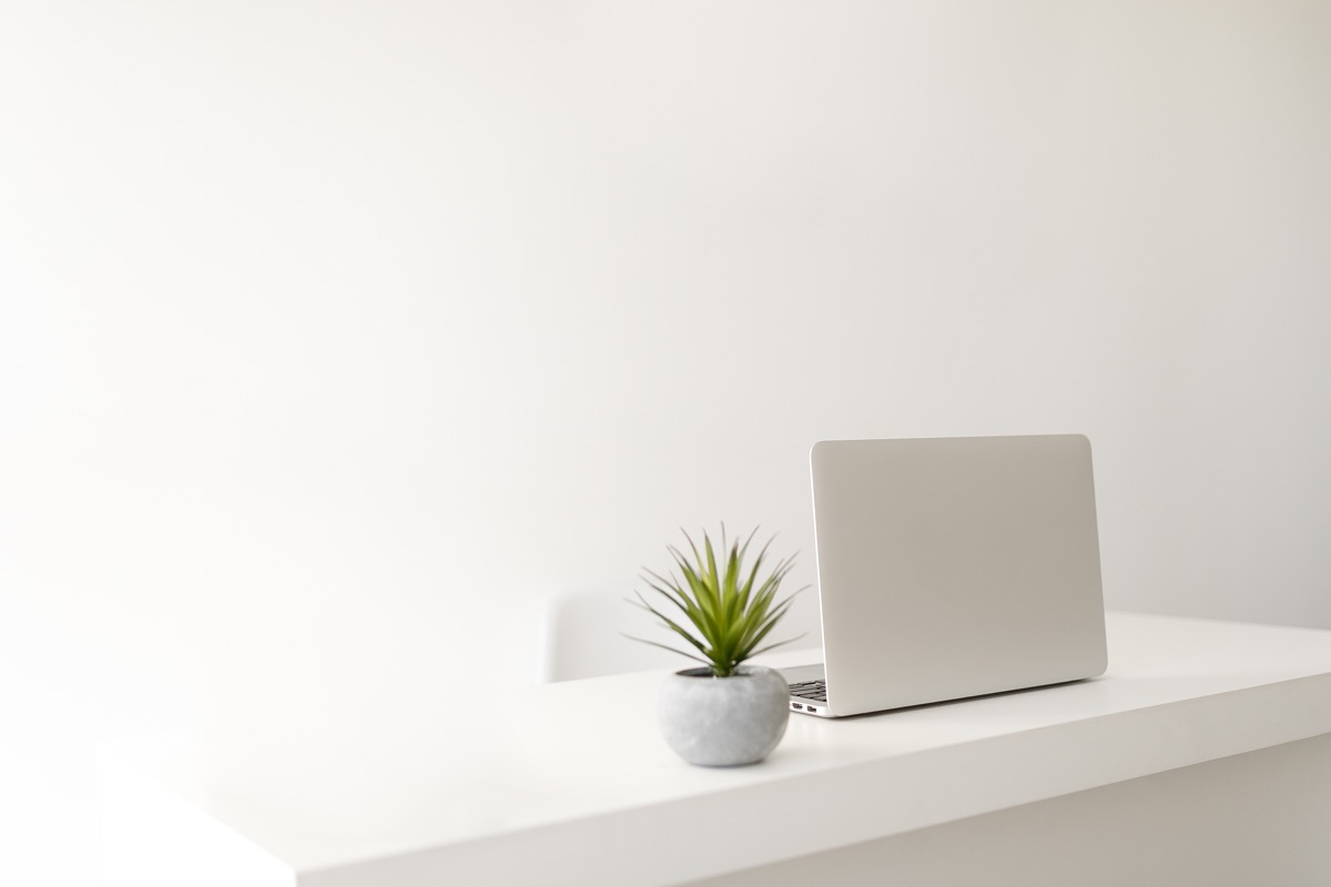 white minimalist home office with laptop of table