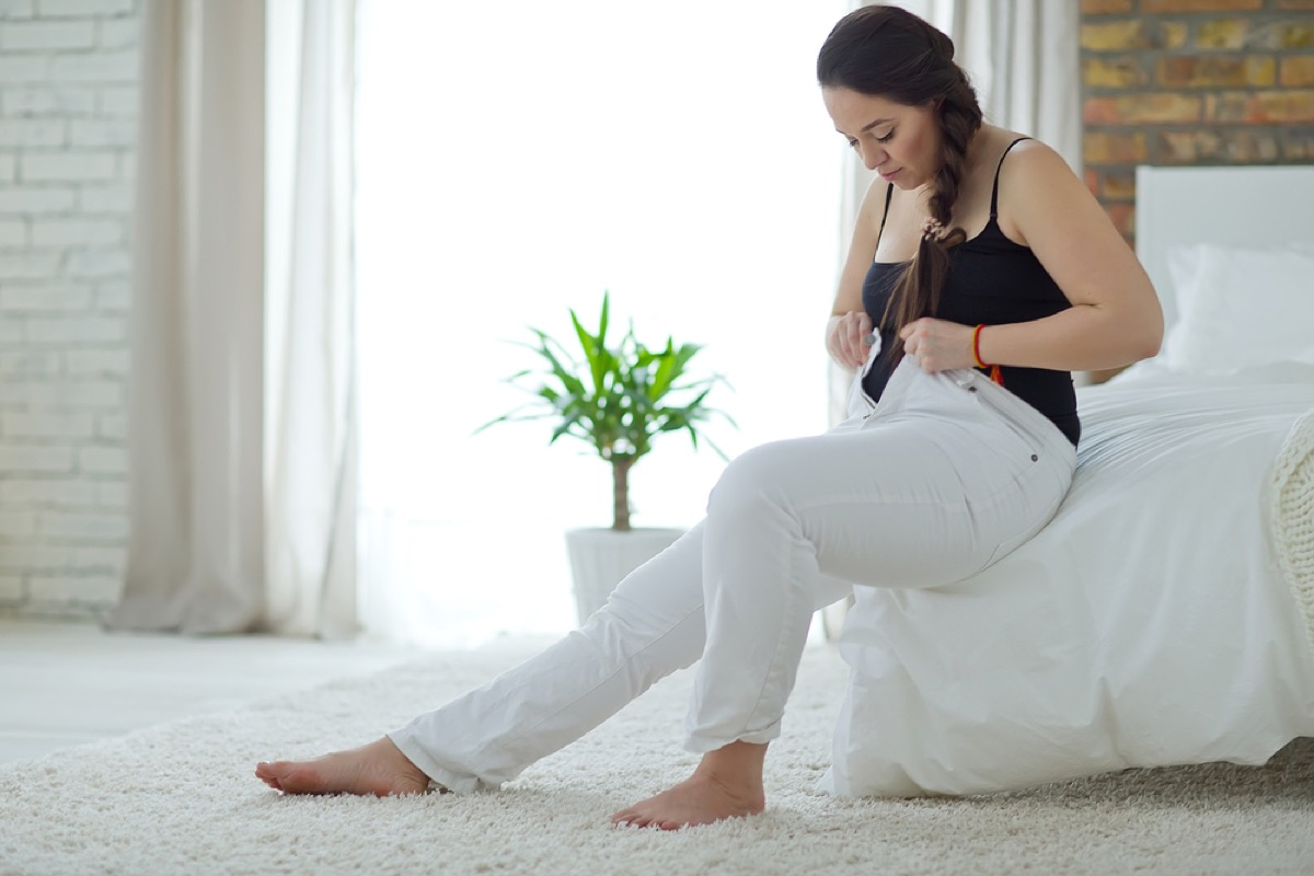 woman buttoning waistband of pants, subtle symptoms of serious disease