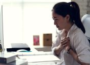 a woman clutching her chest in an office, signs your cold is serious