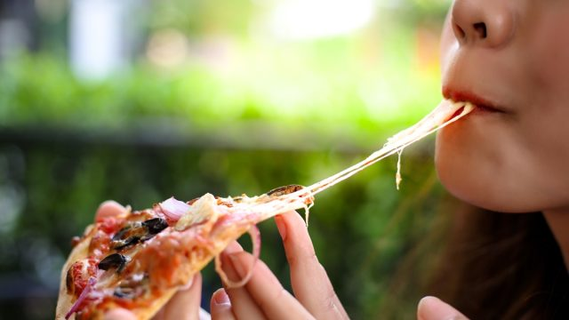 woman eating pizza, healthy sex after 40