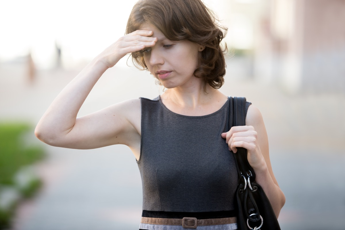 Woman on the Street Holding Her Head and Feeling Dizzy, subtle symptoms of serious disease