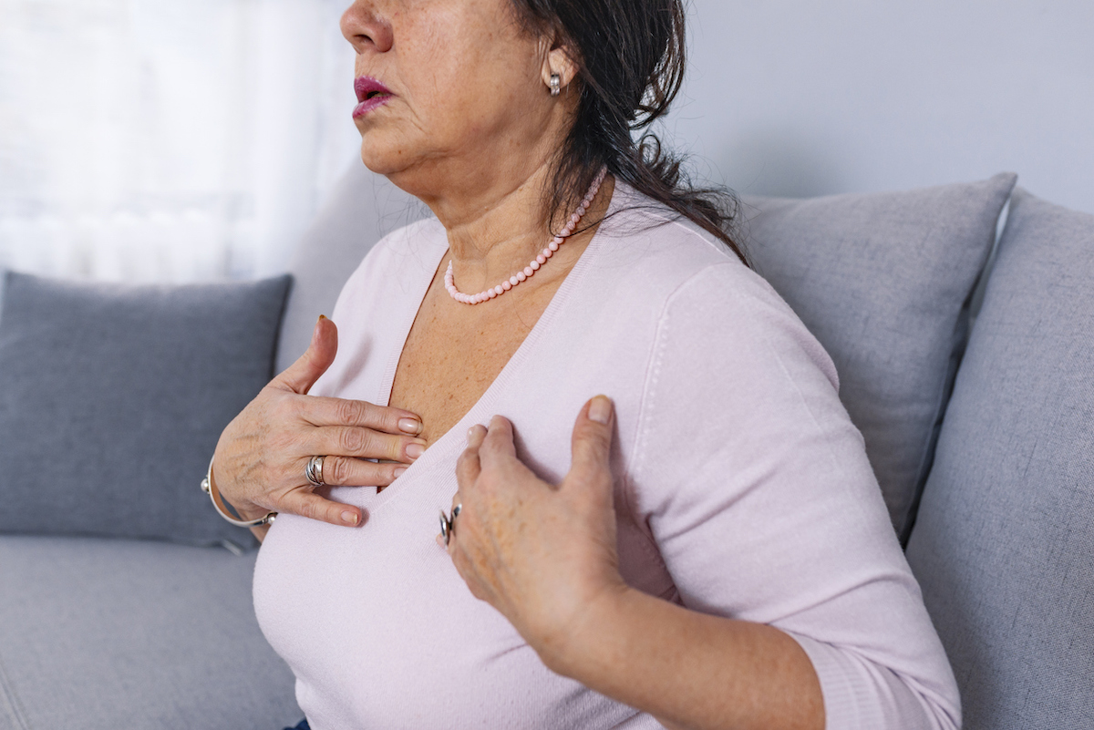 Upset stressed mature middle aged woman feeling pain and ache in chest, could be having heart attack or strok