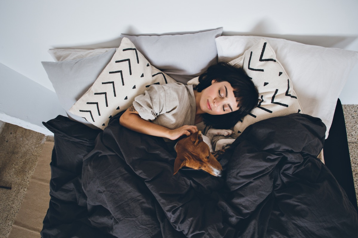 Woman lying under the blanket with her dog