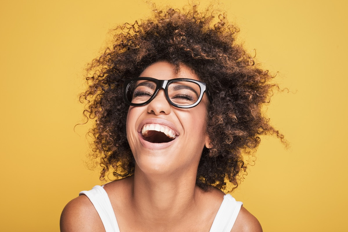 Woman in glasses laughing agains yellow background