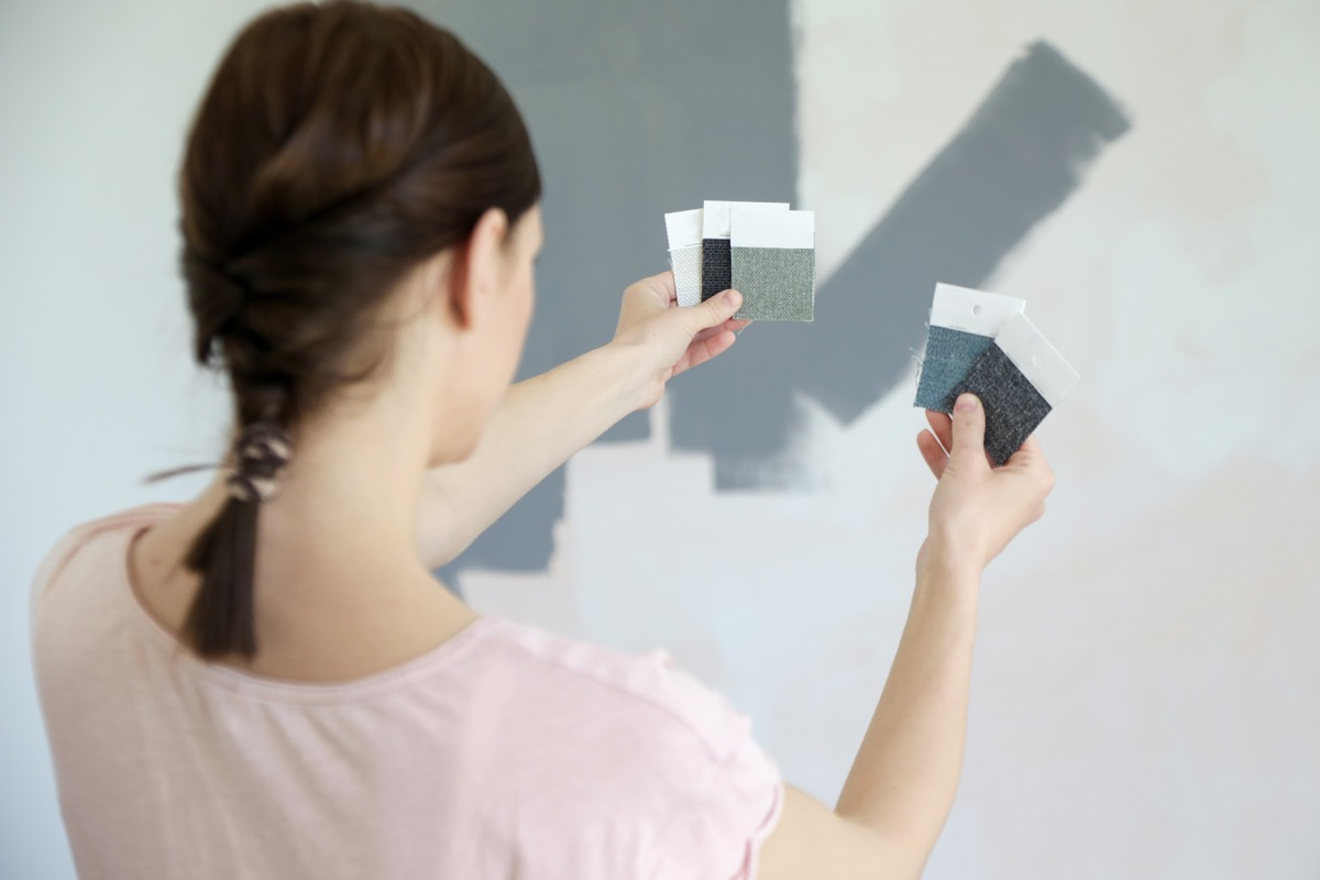 young woman choosing between paint swatches of gray for her wall