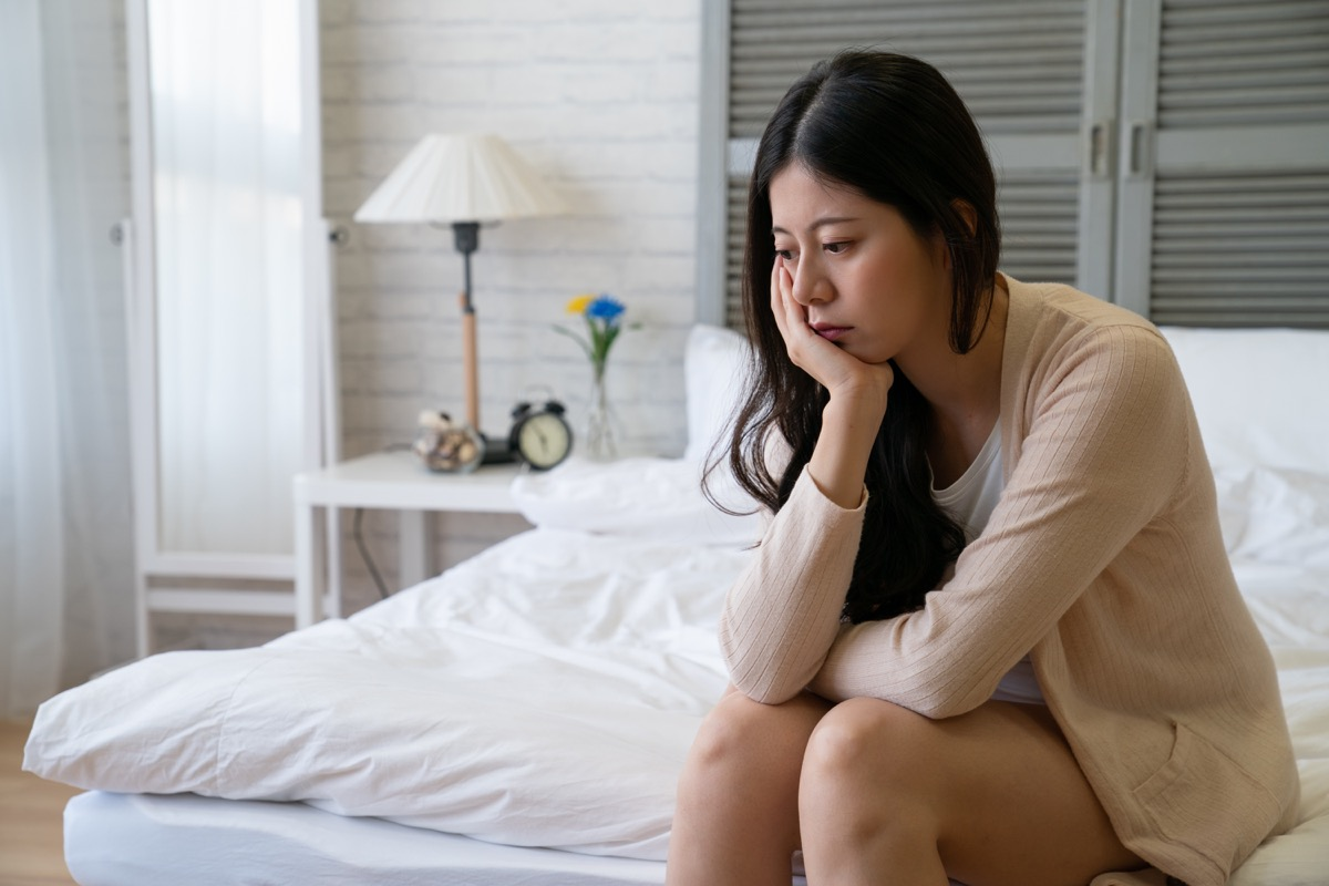 Woman looking sad and depressed in bed