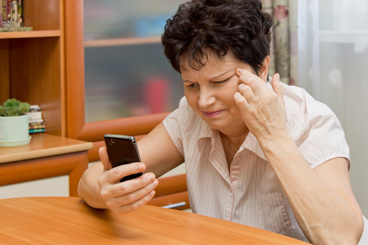 Woman squinting at her phone because she is having trouble seeing