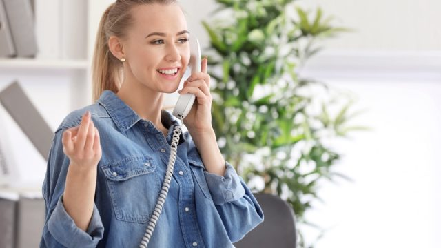 young blonde woman talking on corded home phone