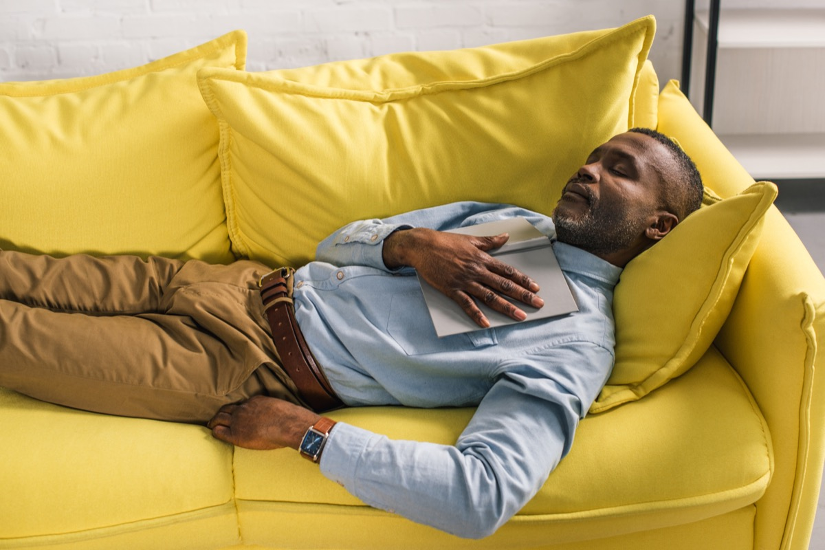 Old black man in khakis and button down napping on yellow couch perfect nap