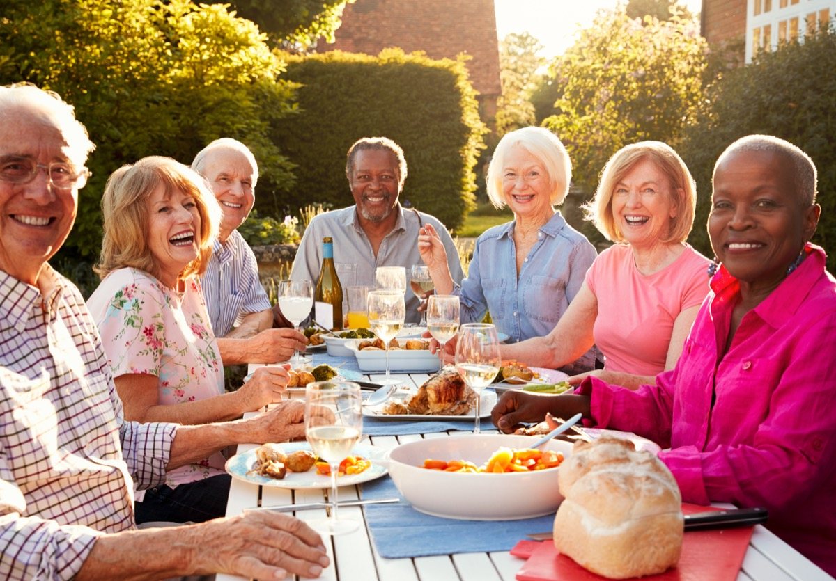 older couples at an outdoor dinner party, etiquette mistakes