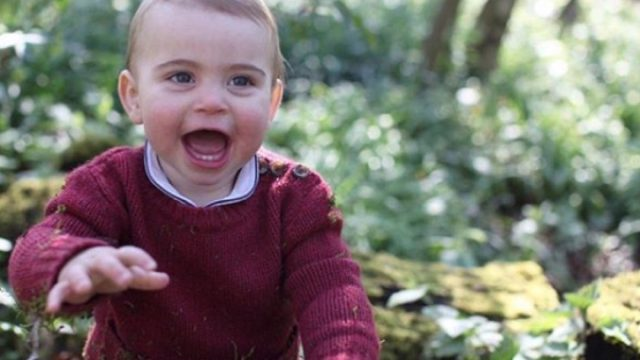 Prince Louis in maroon sweater sits in wooded area, official photo by Kate Middleton