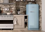 product shot of a baby blue full-size SMEG fridge in a rustic kitchen