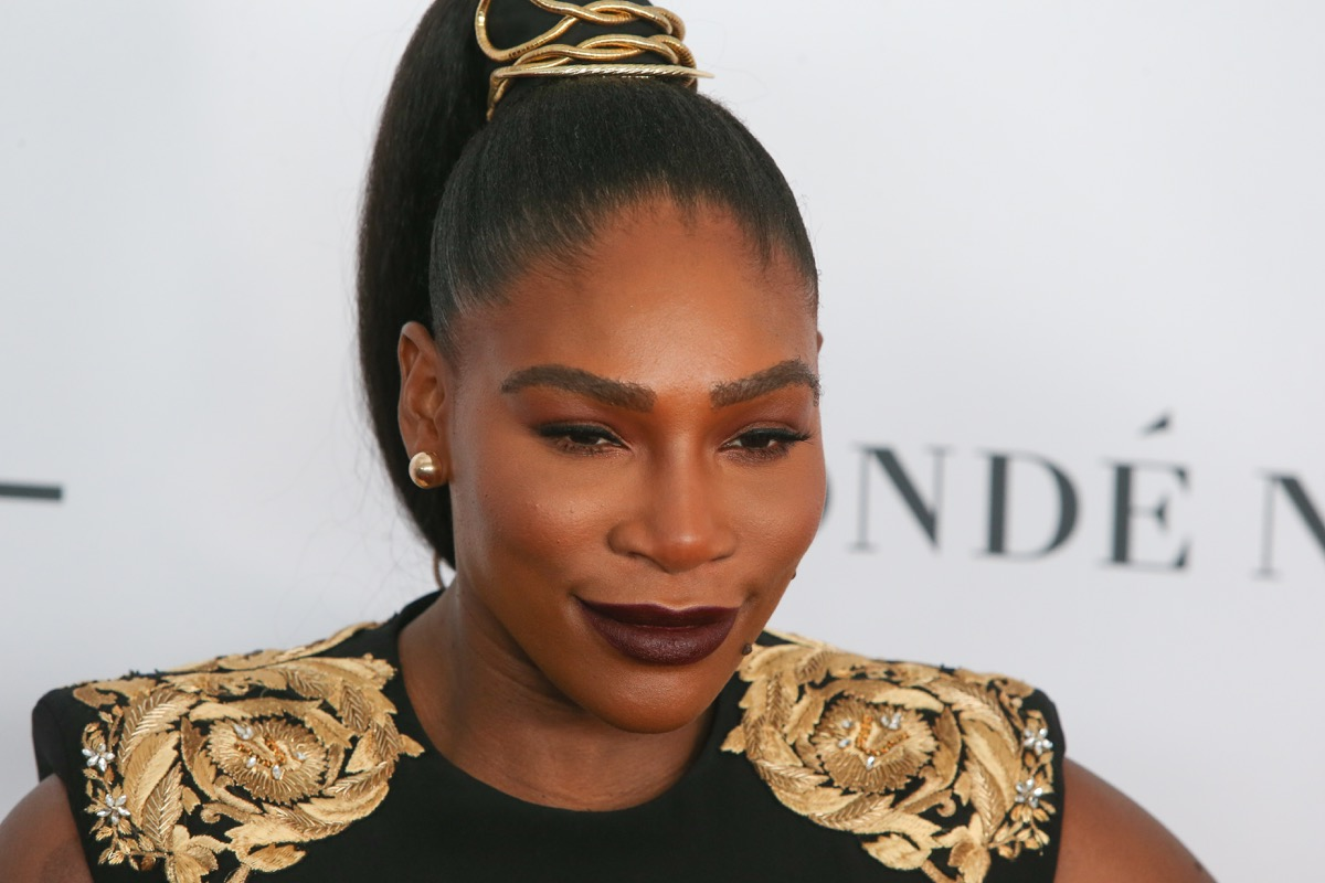 Serena Williams on red carpet in black and gold outfit