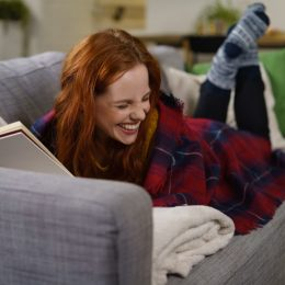 Woman laughing as she reads a book