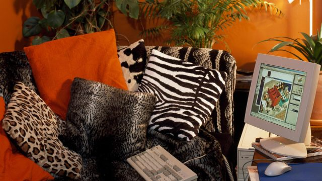 Animal print cushions on sofa in a nineties bed-sitting room with a computer on a low table