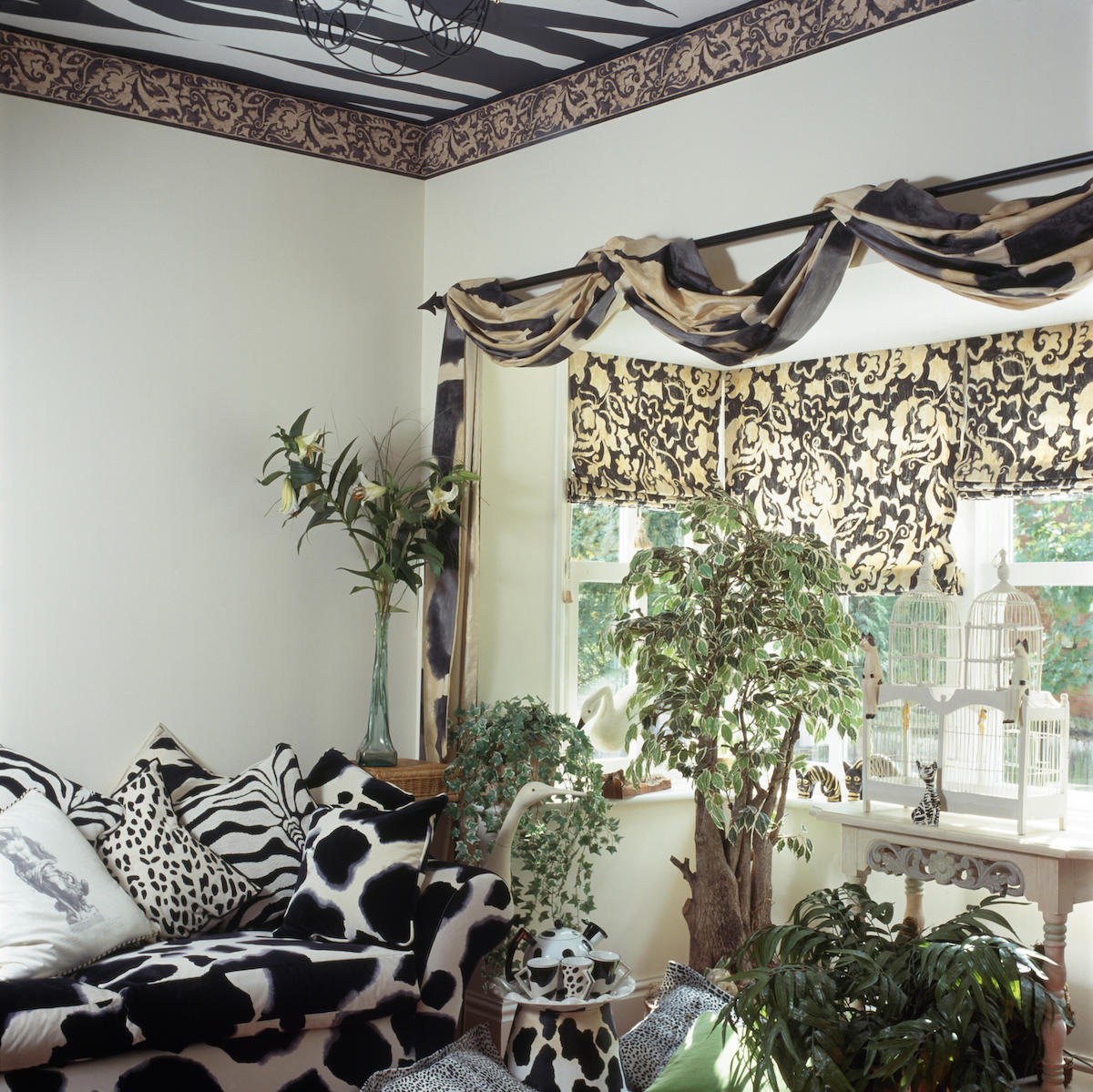 Black+white animal print sofa and cushions in nineties living room with draped fabric on pole above window