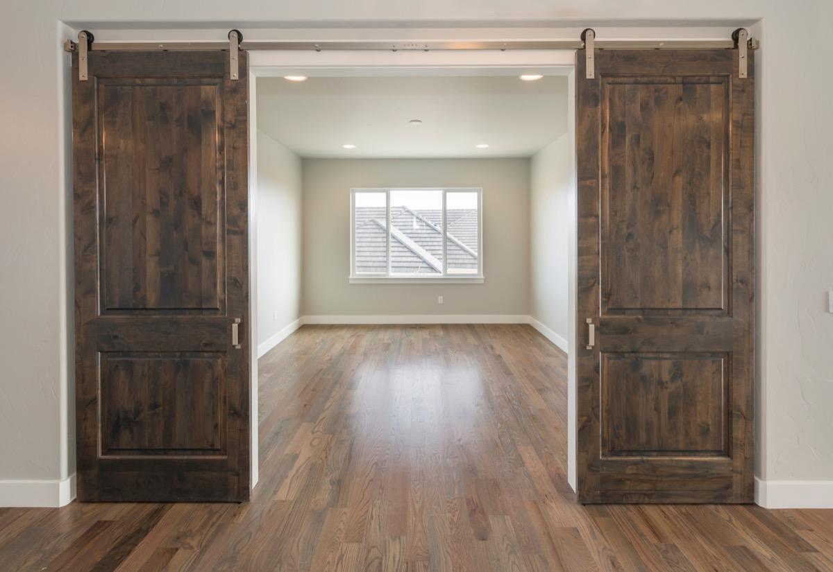 barn doors in home opening onto empty room with window