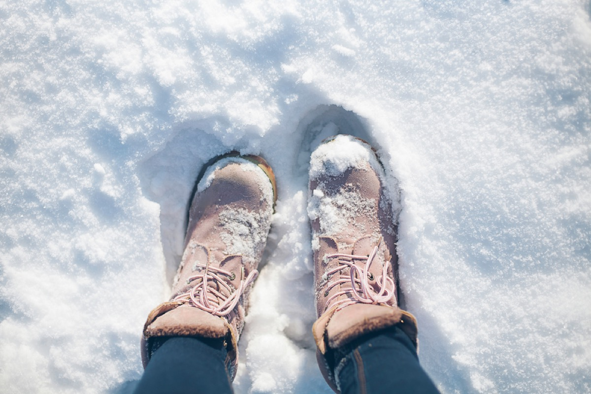 woman walking in snow in pink boots