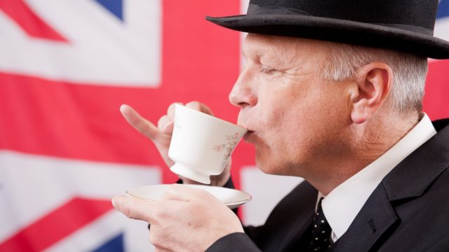 british man drinking tea with flag british words
