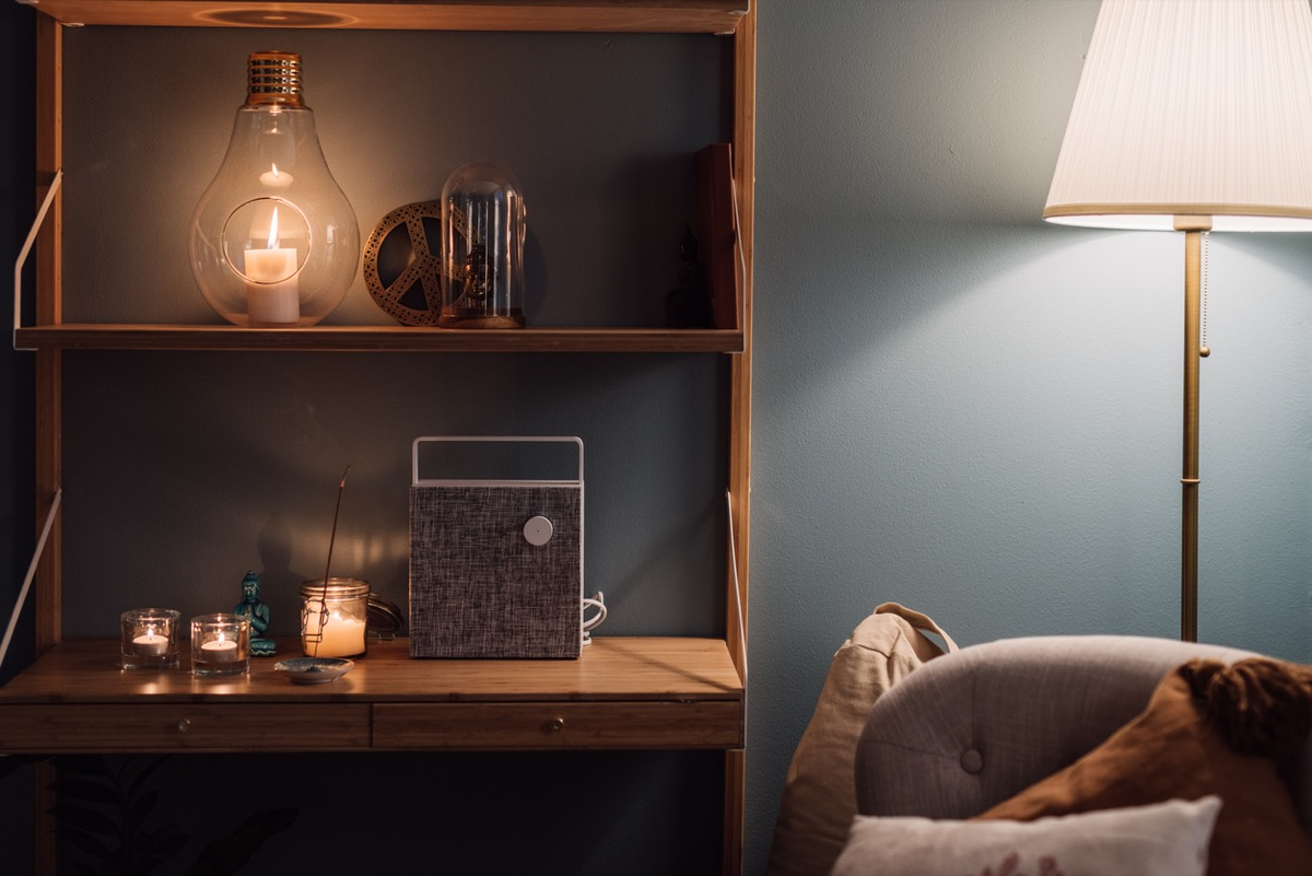 Cozy home interior shelf with candles and bluetooth wireless speaker