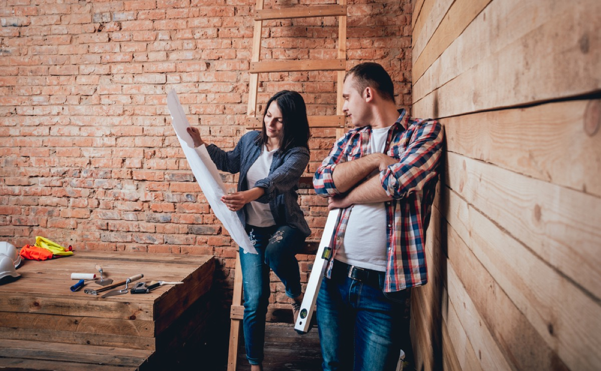 couple looking at blueprints, worst home renovations