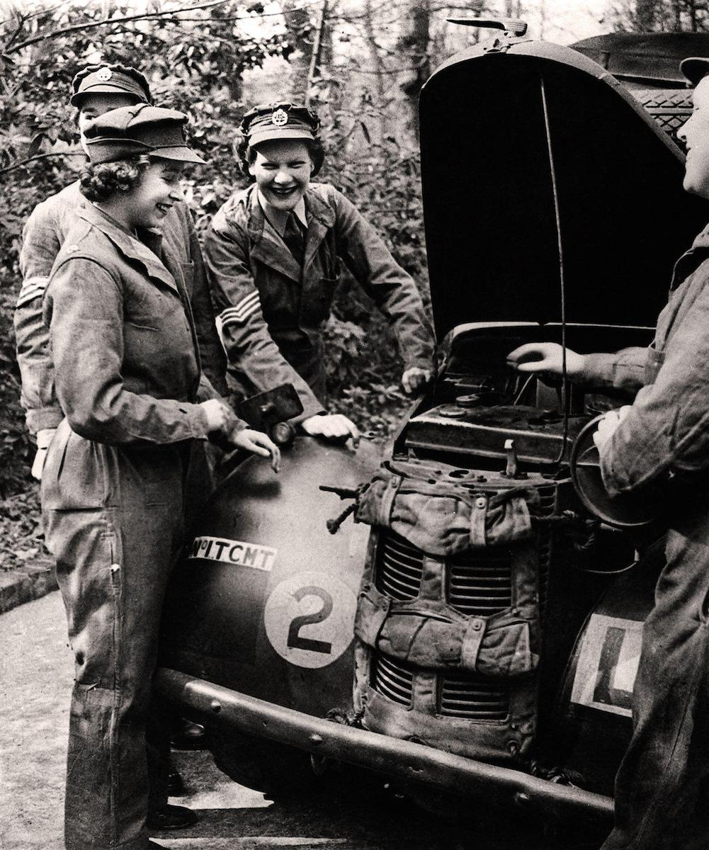 Princess Elizabeth in her uniform of the ATS The Auxiliary Territorial Service, a women's army auxiliary branch, with other smiling ATS service members working on and servicing a British Army military vehicle.